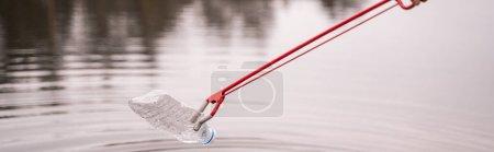 Photo for Grabber picking up plastic bottle from lake, banner - Royalty Free Image