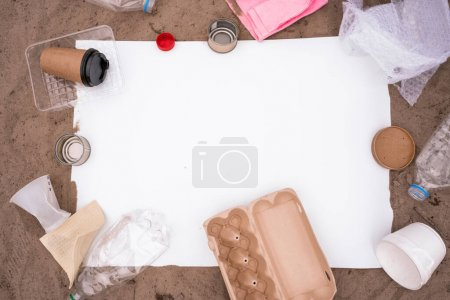 Photo for Top view of blank placard near trash on sand - Royalty Free Image