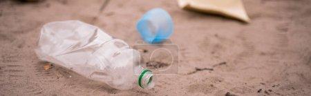 Photo for Plastic bottle near trash on blurred sand, banner - Royalty Free Image