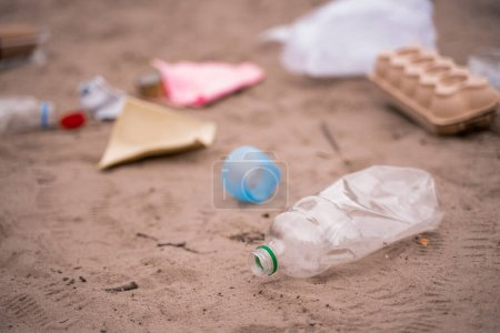 Photo for Plastic bottle near blurred trash on sand - Royalty Free Image