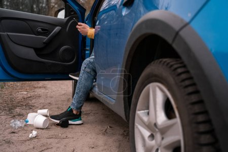 Photo pour Vue recadrée de l'homme debout sur le sol près de la voiture et des ordures, concept écologique - image libre de droit