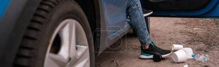 Photo pour Vue recadrée de l'homme debout sur le sol près de la voiture et des ordures, concept écologique, bannière - image libre de droit