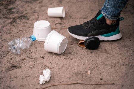 Photo pour Vue recadrée de l'homme debout sur le sol près des ordures, concept écologique - image libre de droit