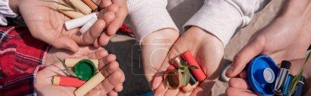 Photo pour Vue recadrée de bénévoles tenant des piles, des bouchons de bouteille et des plantes vertes dans les mains, bannière - image libre de droit