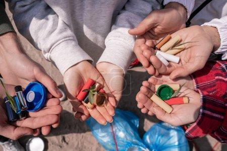 Photo pour Vue recadrée de bénévoles tenant des piles, des bouchons de bouteille et des plantes vertes dans les mains - image libre de droit