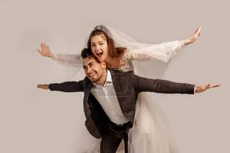 Photo for Cheerful bride piggybacking on happy groom isolated on grey - Royalty Free Image