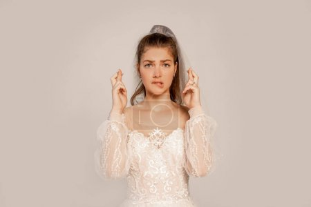 Photo pour Worried woman in wedding dress with crossed fingers isolated on grey - image libre de droit