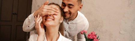 glücklicher Mann, der die Augen einer fröhlichen Freundin mit der Hand bedeckt, während er Blumen hält, Banner