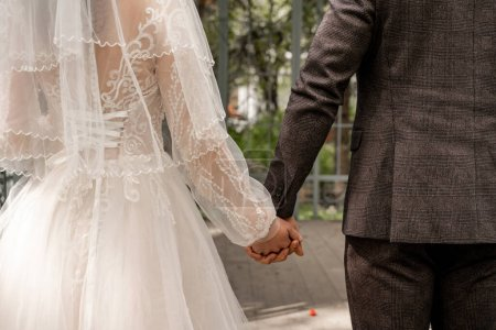 Photo pour Partial view of newlyweds holding hands outdoors - image libre de droit
