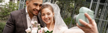 Photo pour Happy bride taking photo with groom on digital camera outdoors, banner - image libre de droit