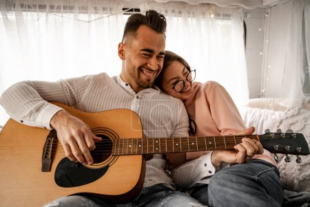 cheerful man playing acoustic guitar near laughing woman in trailer
