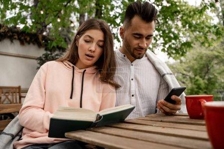 Photo pour Pretty woman reading book near man chatting on smartphone outdoors - image libre de droit