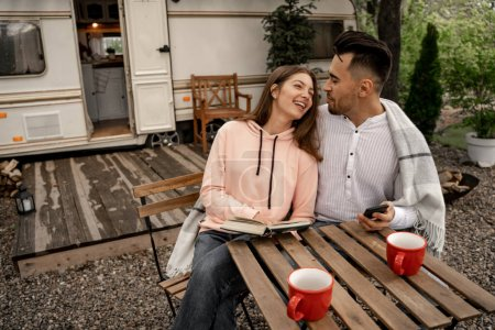 Photo for Young woman with book laughing near man with smartphone near camper - Royalty Free Image