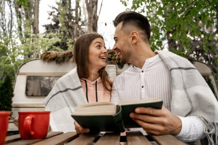 Photo pour Cheerful couple looking at each other while sitting with book in camping - image libre de droit