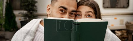 Photo for Joyful couple obscure faces with book while looking at camera outdoors, banner - Royalty Free Image