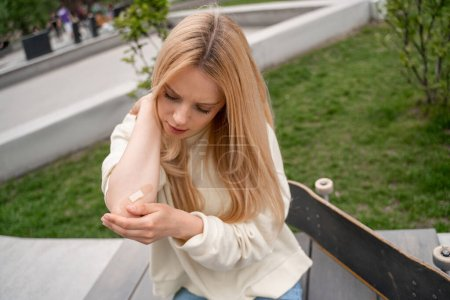 Photo for Blonde woman applying adhesive plaster on injured elbow near skateboard on bench - Royalty Free Image