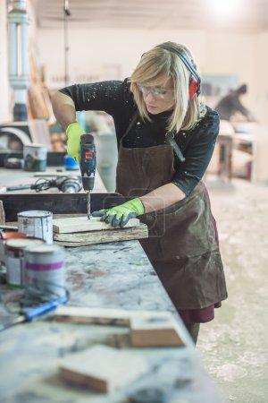 Female carpenter using power drill