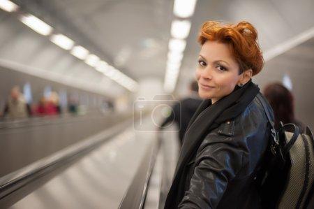 Mujer en la escalera mecánica del metro tounel