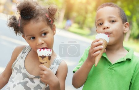 Photo for Adorable brother and sister eating ice cream cone on the street - Royalty Free Image