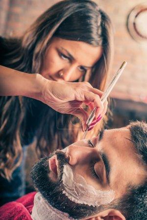 Photo pour Femme coiffeuse rasant la barbe d'un client dans un salon de coiffure. Gros plan - image libre de droit