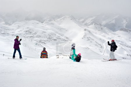 Happy snowboarders and skiers enjoy on top of mountain