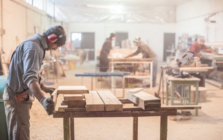 Photo for Carpenter work on wood plank in workshop - Royalty Free Image