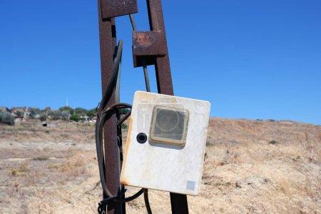 Photo pour Gros plan d'une vieille boîte à fusibles en plastique sale sur un vieux lampadaire en métal rouillé, couché doucement sur le côté. - image libre de droit