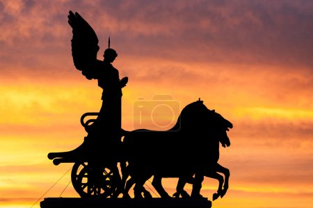 Rome at dusk: silhouette of the goddess Victoria over the National Monument to Vittorio Emanuele II