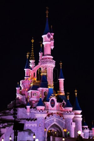 Photo pour Disneyland Paris Castle illuminated at night. Disneyland Paris is a holiday and recreation resort in Marne-la-Vallée, a new town in the eastern suburbs of Paris, France. With 15,405,000 combined visi - image libre de droit