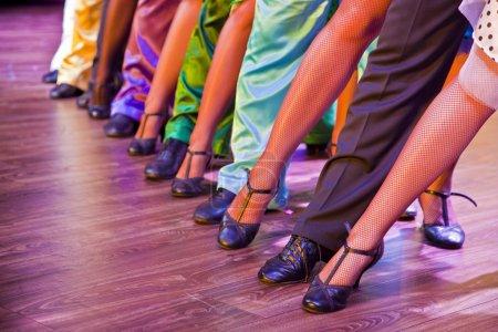Photo pour Jambes de danseur sur scène dans des costumes colorés - image libre de droit