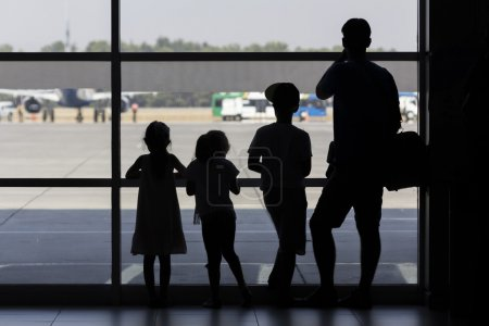 Family silhouette in front of window at airport looking at planes landing