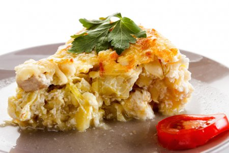 Casserole, squash and meat, fried with cheese, cottage cheese in a glass.