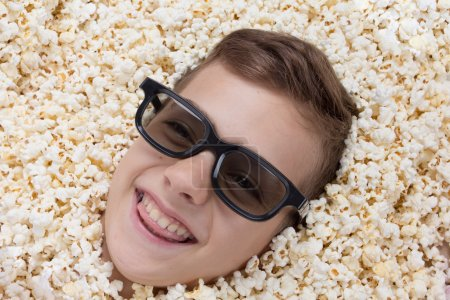 Laughing young boy in stereo glasses watching a mo...