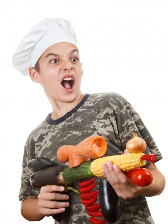 Humorous portrait of a teen boy chef with rifle vegetables, screaming cheers