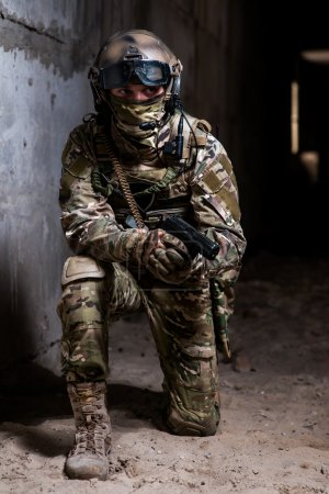 Military man in camouflage with a gun standing knee in the building and monitors the aim