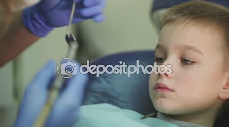 Closeup little kid during procedure of teeth drilling treatment at dentist clinic office.
