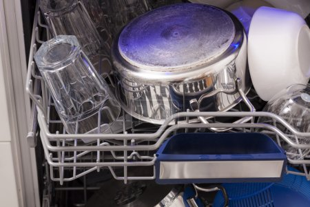 Dishwasher loades in a kitchen with clean dishes a...