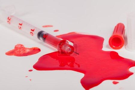 Spritze spritzt rotes Blut auf weißem Hintergrund