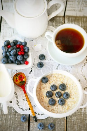 Foto de Porridge with blueberry and cup of tea on the vintage napkin on the white wooden background, Russian style spoon in desaturated tone, moody lighting - Imagen libre de derechos