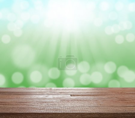 Wood table top on green blurred bokeh light and sun ray
