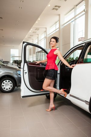 Beautiful girl in a short skirt is standing next to a white car in the showroom