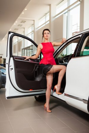 Photo for Beautiful girl in a short skirt is standing next to a white car in the showroom - Royalty Free Image