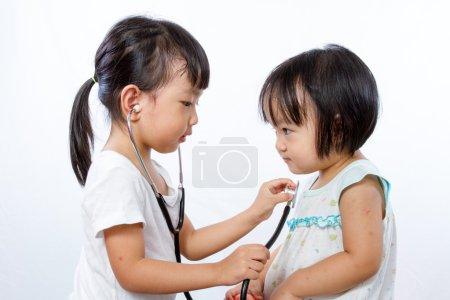 Photo pour Asiatique petites filles chinoises jouer comme médecin et patient avec stéthoscope isolé sur fond blanc - image libre de droit