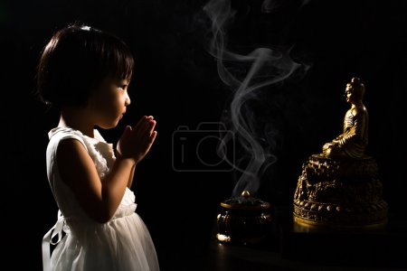 Asian Little Chinese Girl Praying in front of Buddha