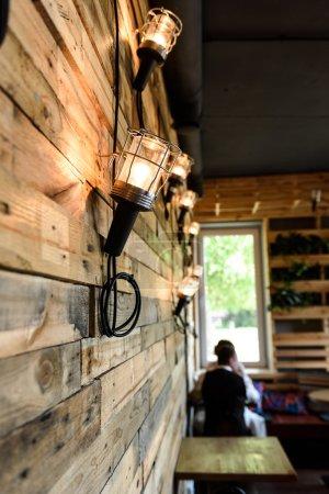 Photo pour Café intérieur en bois avec des lampes sur le mur - image libre de droit