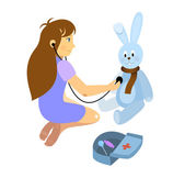 Little girl playing a doctor with plush teddy rabbit toy