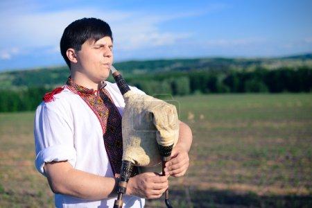 Portrait of man enjoying playing pipes in Ukrainia...