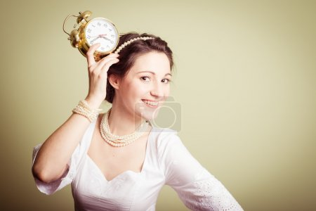 Young lady in white dress having fun holding clock up on head