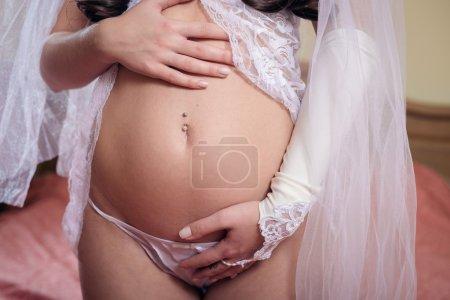 Photo pour Gros plan image sur tenant la main sur ventre nu enceinte belle mariée portant lingerie sexy - image libre de droit