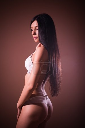 Elegant buns: gorgeous sexy lady black hair glamor pinup girl with excellent fitness bum happy posing relaxing standing half back to camera & looking down shy on copy space background portrait image
